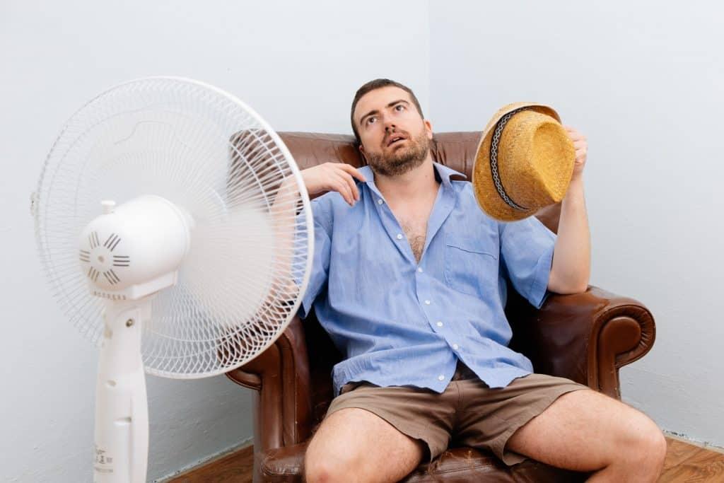 homem sentindo calor sentado em frente a um ventilador
