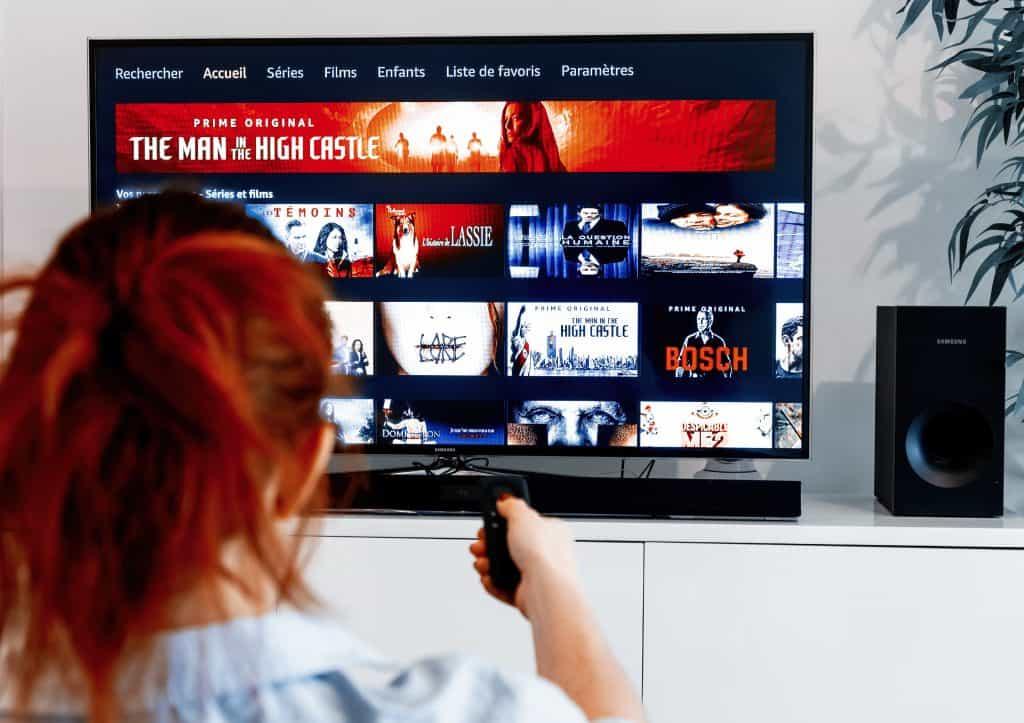 garota mexendo em controle da TV acessando plataforma de streaming