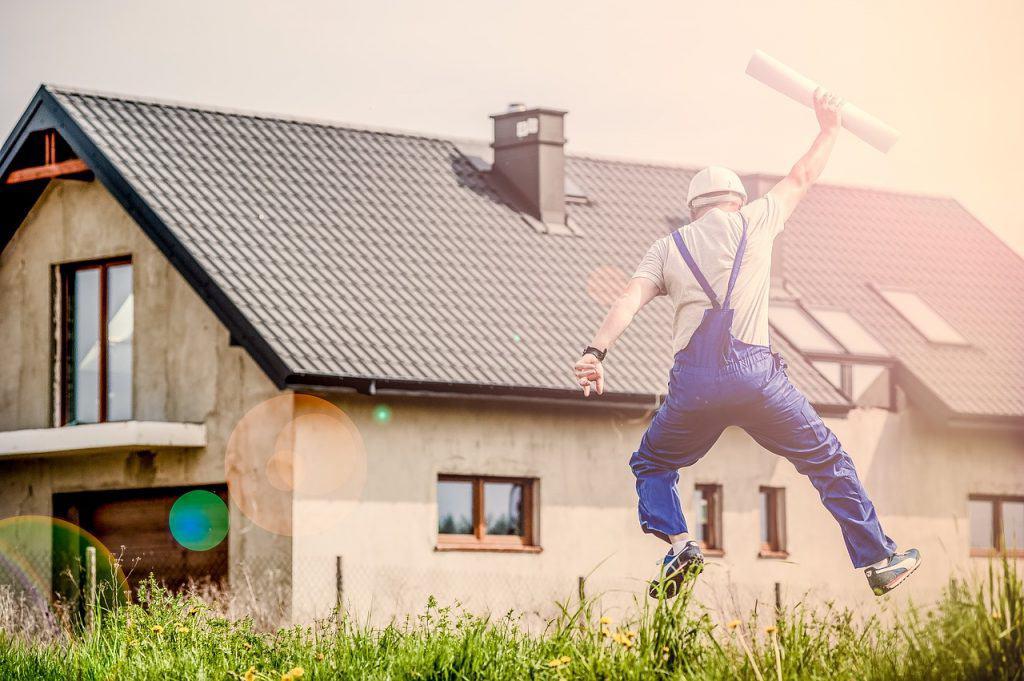 homem com uniforme de trabalhando dando um salto em frente a uma casa