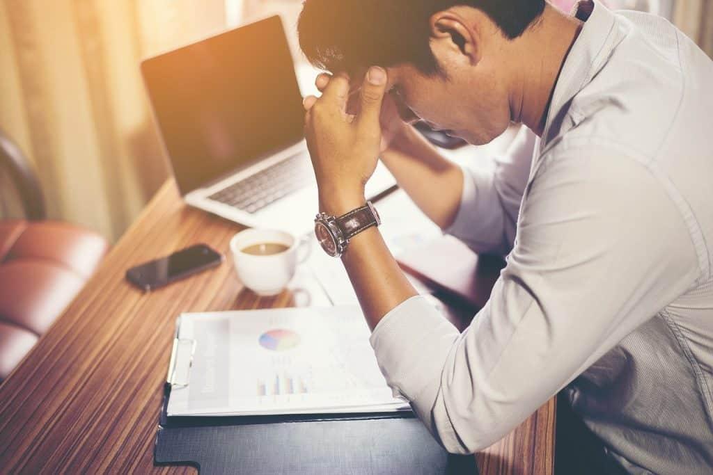 homem de cabeça baixa em frente a um notebook