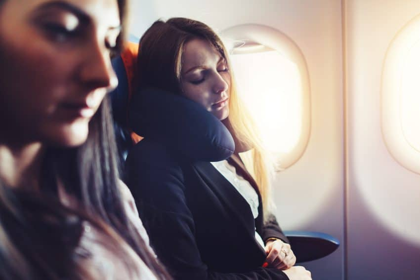 Duas mulheres dormindo no avião, uma delas está usando um travesseiro de pescoço.