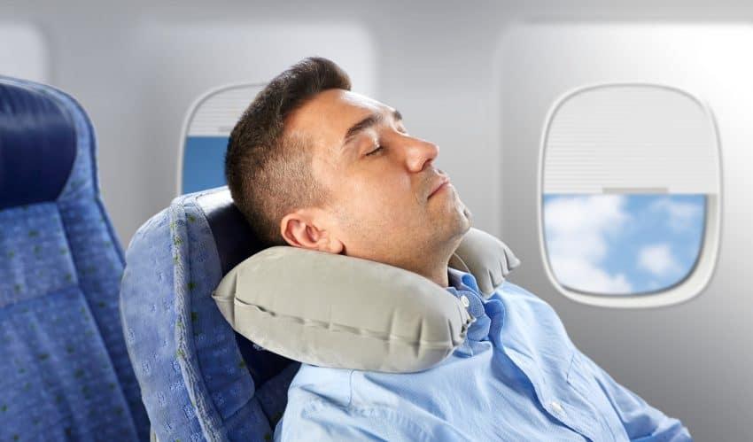 homem dormindo em avião com travesseiro de pescoço inflável