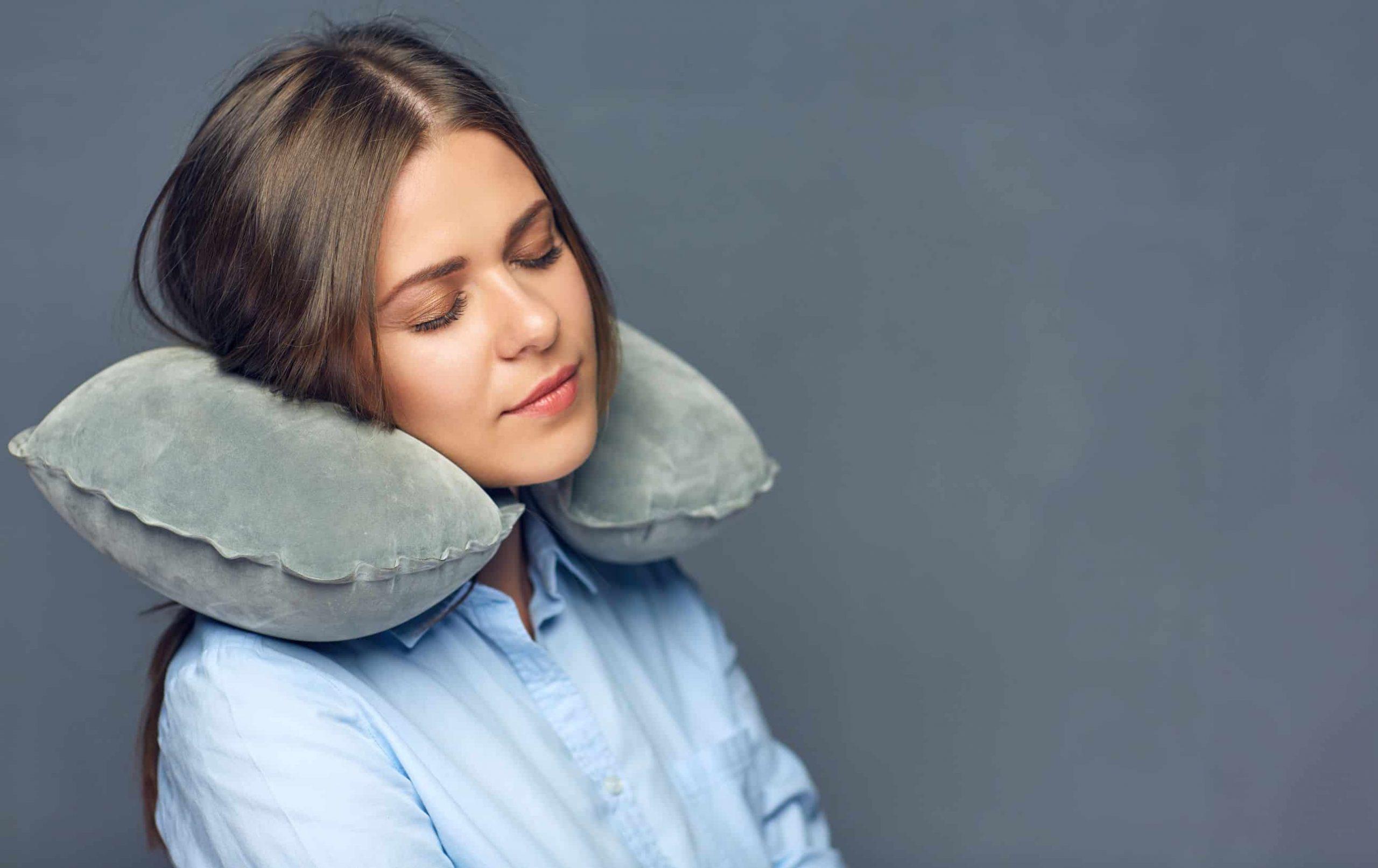 Imagem de mulher utilizando um travesseiro de pescoço.