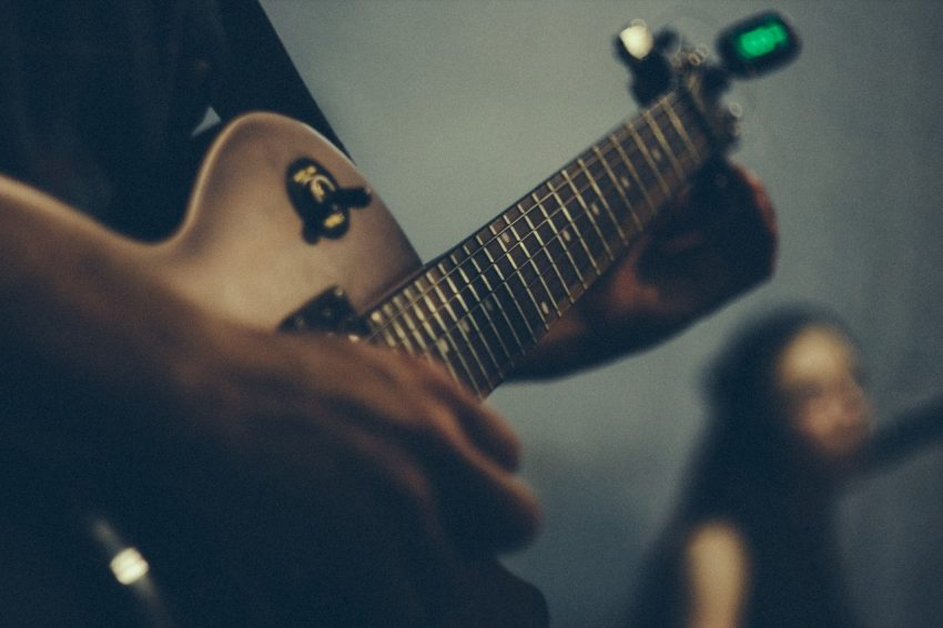 Image of a person tuning a guitar with a clip tuner attached to the end.