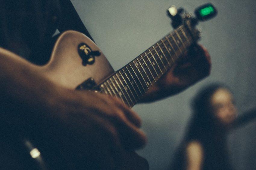 Imagem de uma pessoa afinando uma guitarra com um afinador de clipe grudado à ponta.