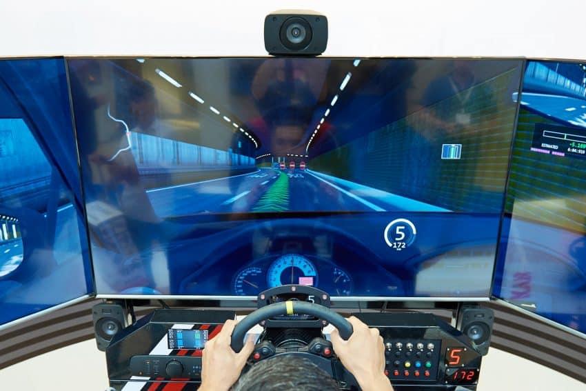 Imagem de uma mão masculina dirigindo um volante para PC em uma grande mesa de jogo.