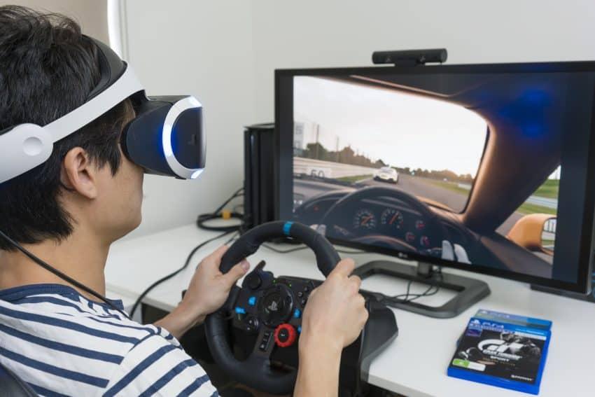 menino jogando corrida no playstation usando um volante para pc