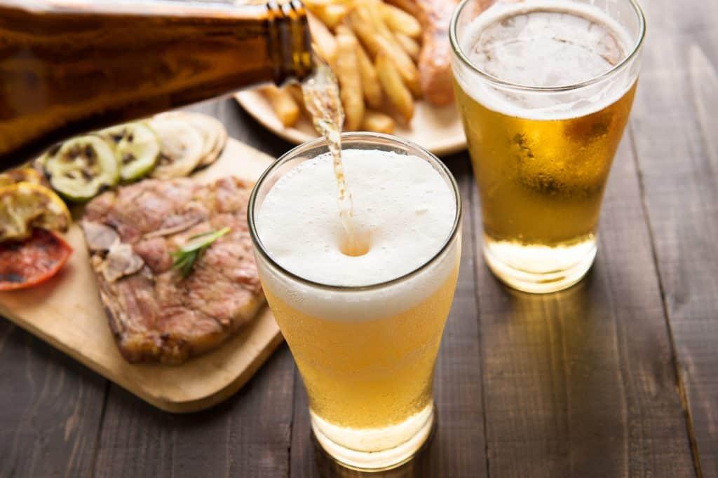 Garrafa servindo cerveja gelada com comida ao fundo