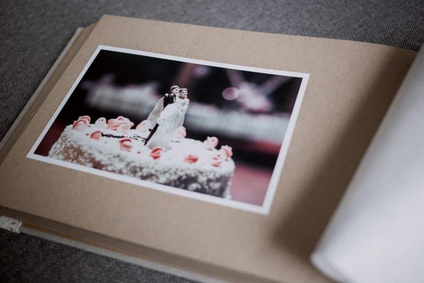 Foto de um álbum de fotos de casamento, em uma página com uma foto do bolo.