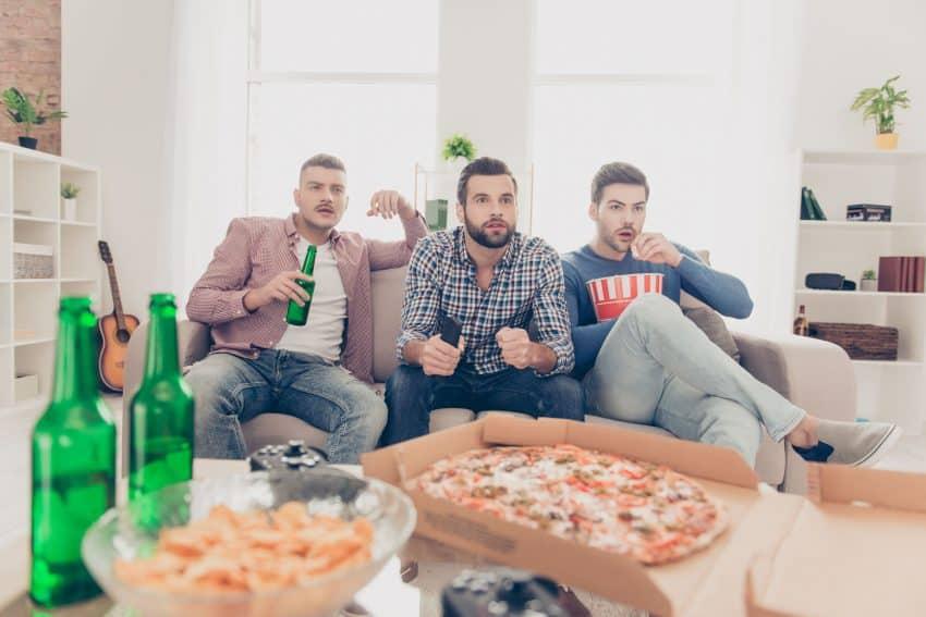 Amigos bebendo cerveja e comendo pizza enquanto assistem TV.