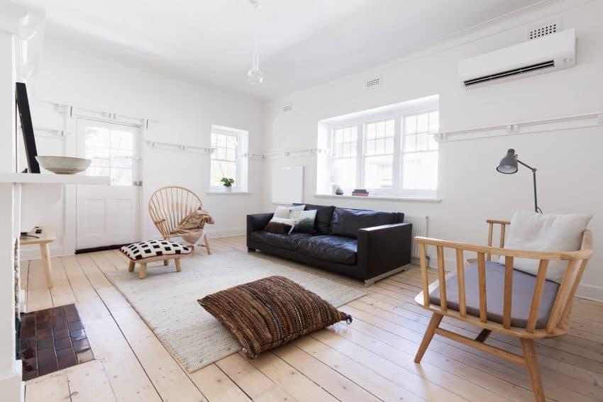 imagem de uma sala bem espaçosa, iluminada e decorada com sofá preto, cadeiras, tapete, almofada e ar condicionado