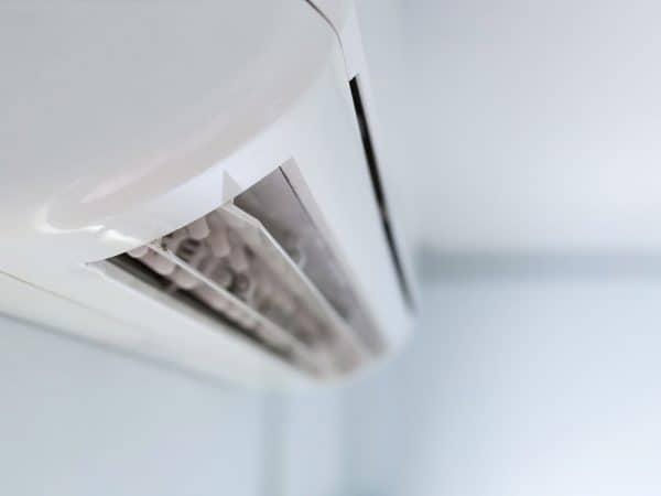 Foto de um ar condicionado de teto branco, em um fundo com blur.