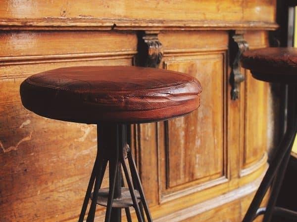 Imagem de duas banquetas com base de metal e assento de couro marrom junto a um bar de madeira ornamentado.