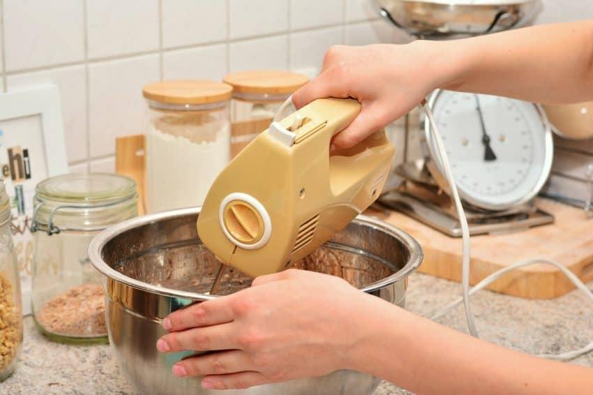 Imagem mostra as mãos de uma pessoa usando a parte superior da batedeira para bater alguma massa dentro de uma tigela de inox.