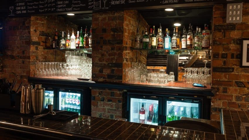Imagem mostra um bar com diversas garrafas de bebidas em uma prateleira, alguns copos na parte de baixo, e abaixo algumas geladeiras com cervejas e vinhos.