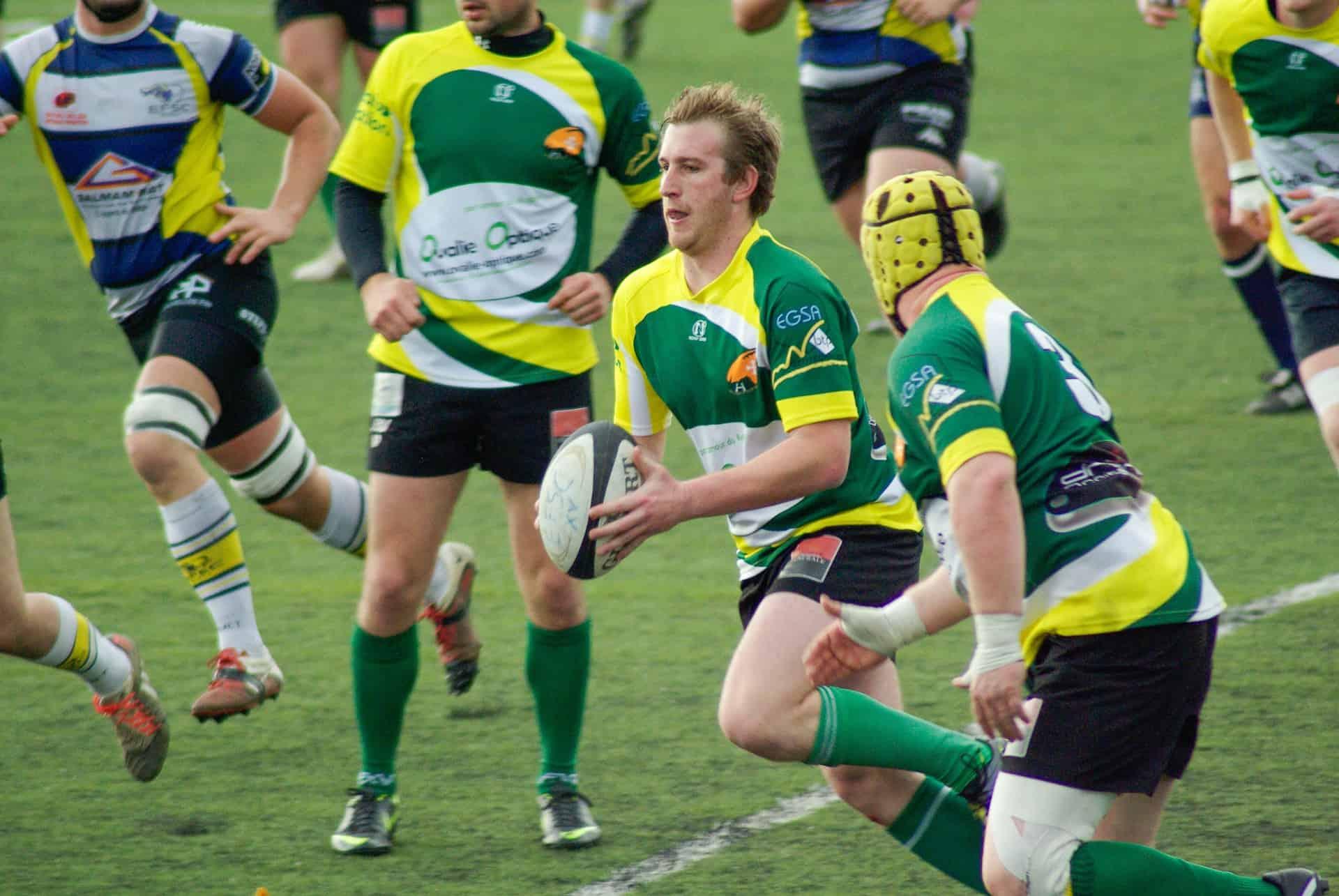 Jogador de camisa verde, amarela e branca carregando uma bola de rugby.