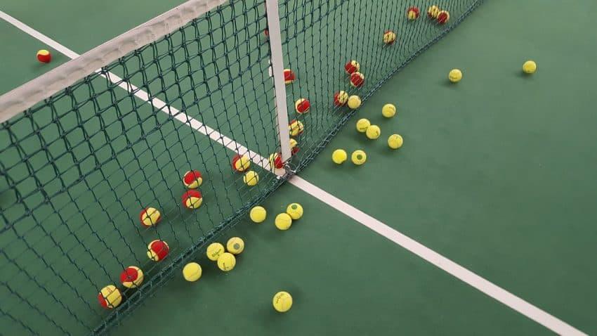 Bolas de tênis espalhadas em uma quadra de tênis com rede.