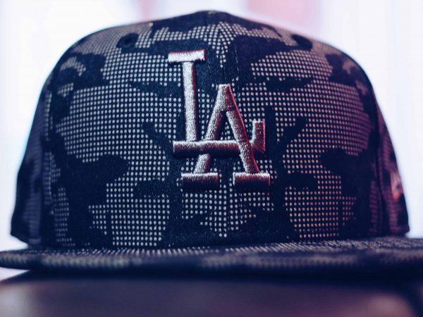 """Imagem mostra um close de um boné aba reta, com um desenho pontilhado e uma estampa grande, escrita """"LA""""."""