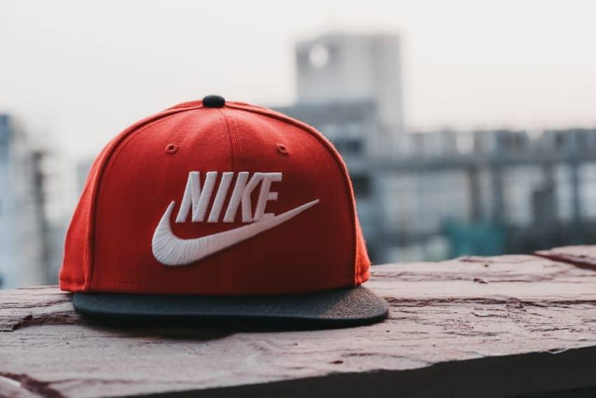 Imagem mostra um close de um boné da Nike, colorido, com uma estampa grande e estilo clean. Ao fundo, um skyline desfocado.