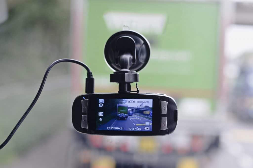 Câmera automotiva com suporte de ventosa em para-brisa filmando trânsito
