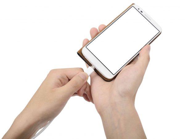Imagem mostra uma mão segurando um smartphone enquanto a outra conecta um cabo micro USB.