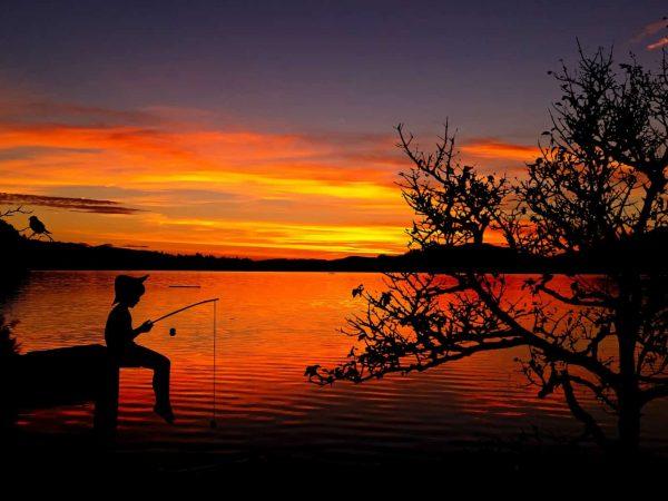 Menino pescando em um lago, enquanto o sol se põe.