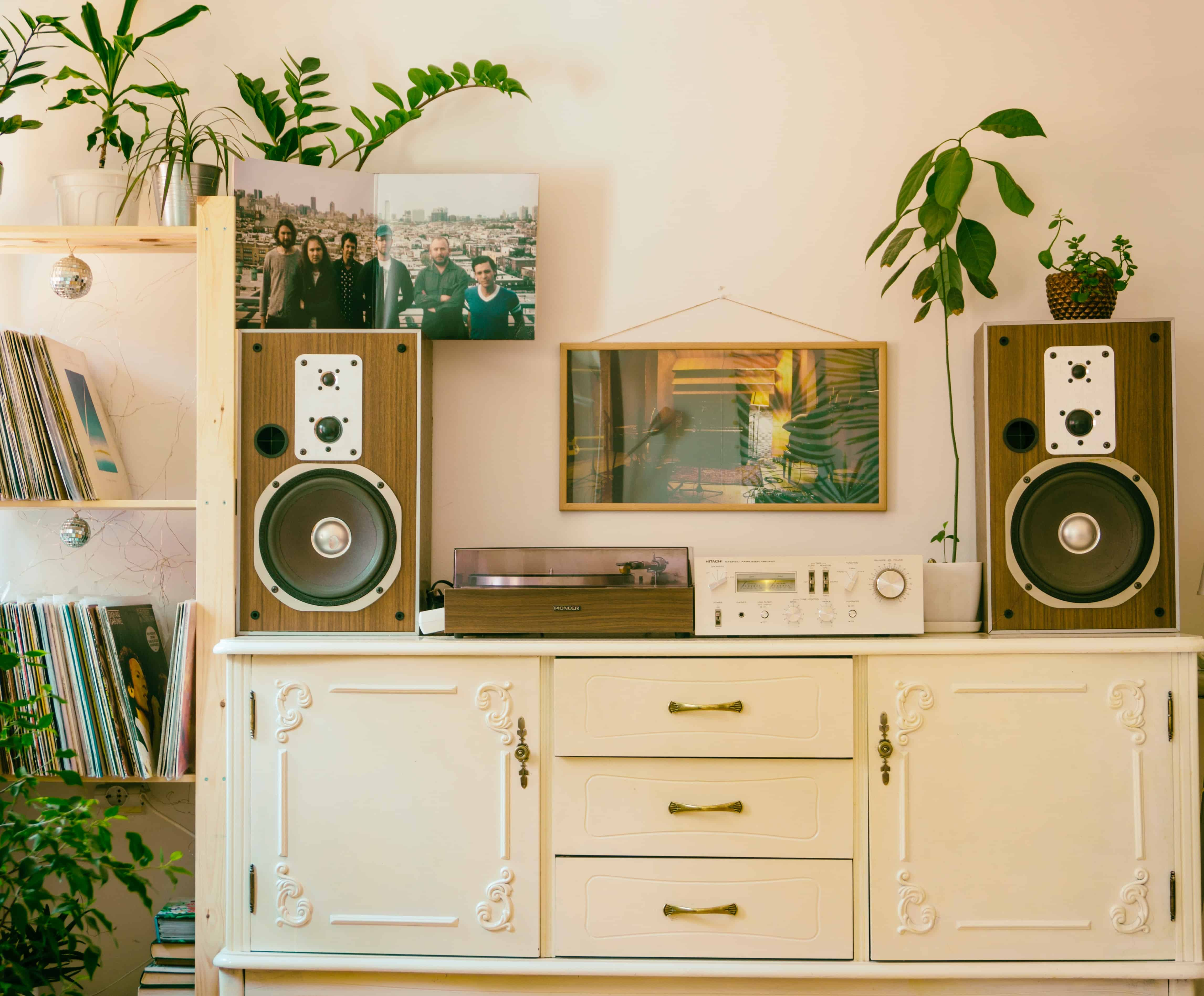 Imagem de uma aparador com tocador de vinil e caixas de som estilo vintage.