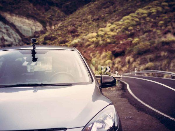 carro com uma câmera veicular estacionado no acostamento da estrada.