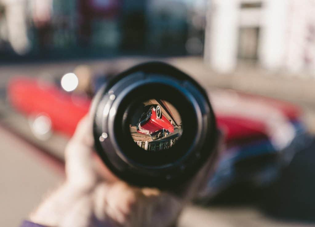 Uma câmera veicular na mão de uma pessoa com a lente apontada para um carro