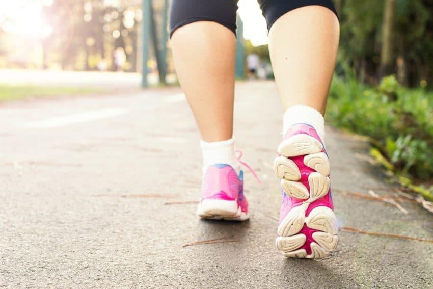 Imagem de caminhada com foco nos pés calçados com tênis e a luz do sol passando entre as panturrilhas.