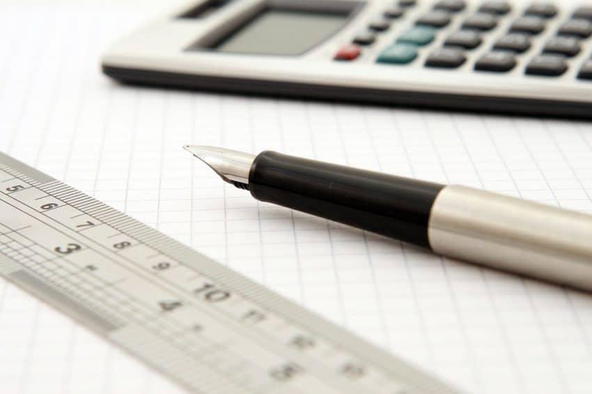 Imagem de régua técnica de plástico transparente com caneta tinteiro e calculadora digital sobre papel quadriculado branco.