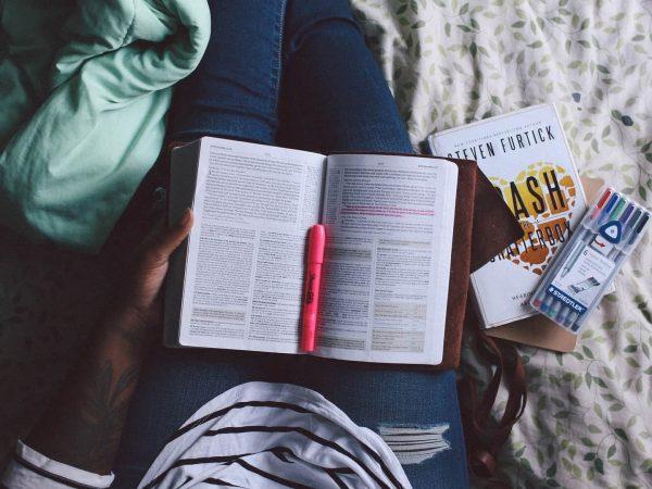 Imagem de pessoa segurando um livro aberto sobre o colo com uma caneta marca texto cor de rosa.