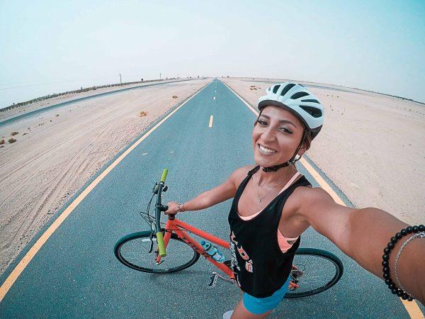 Imagem mostra uma mulher vestindo um capacete e segurando uma bicicleta em uma estrada.