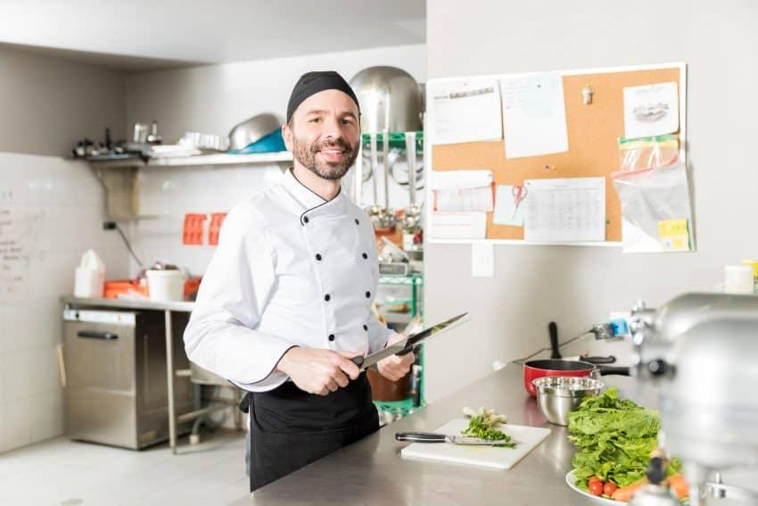 Chef de cozinha afiando uma faca, há alimentos na bancada.