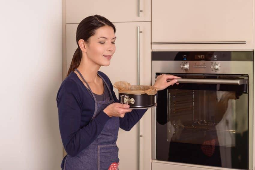 Mulher colocando bolo no forno embutido para assar.
