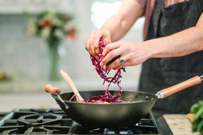 Imagem de uma pessoa colocando repolho roxo em uma panela de ferro, que já está no fogão.