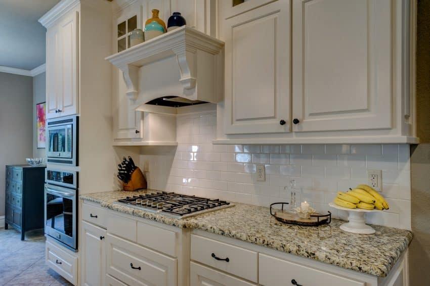 A fotografia mostra uma cozinha moderna, o forno embutido está localizado à direita da imagem.