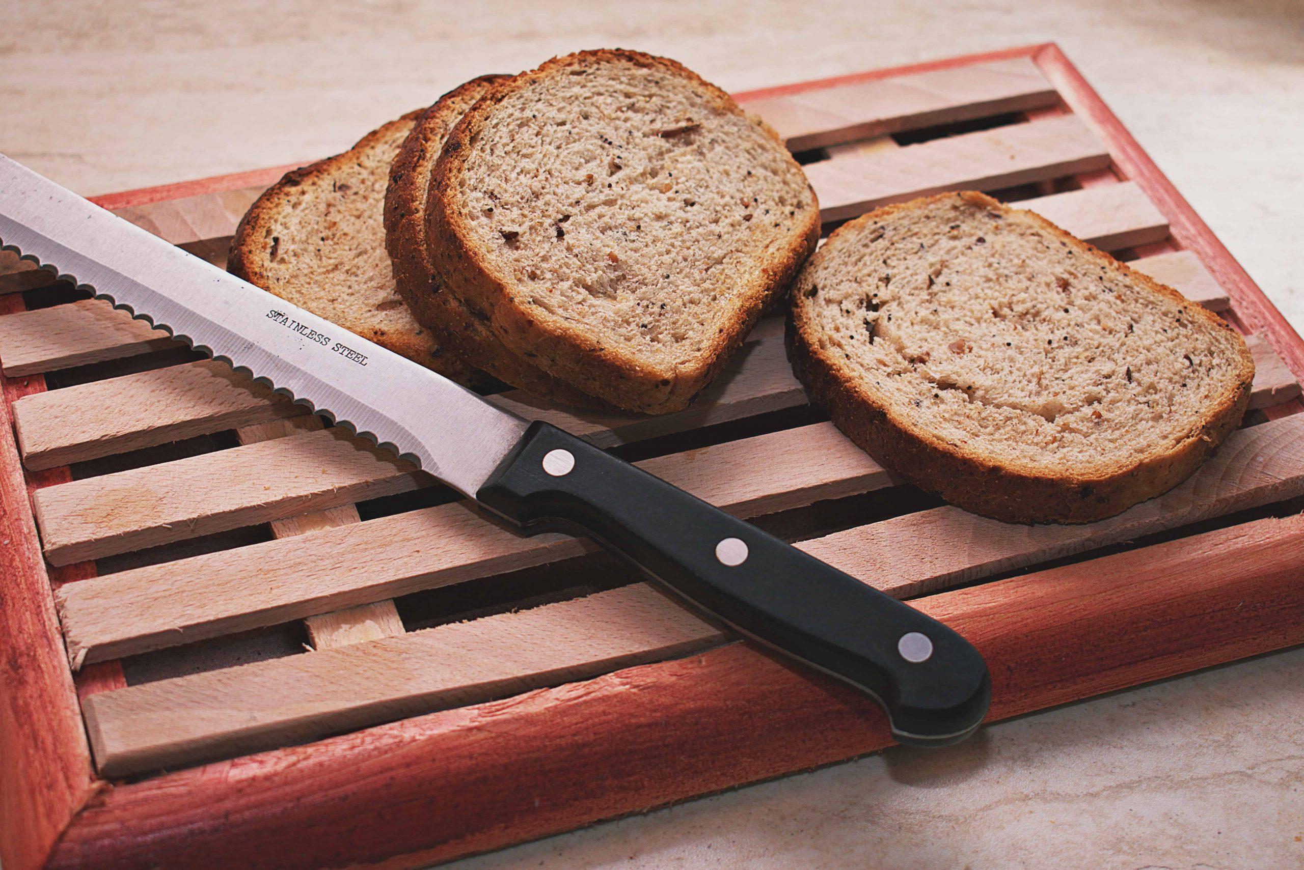 Foto de quatro fatias de pão ao lado de uma faca de cortar pão.