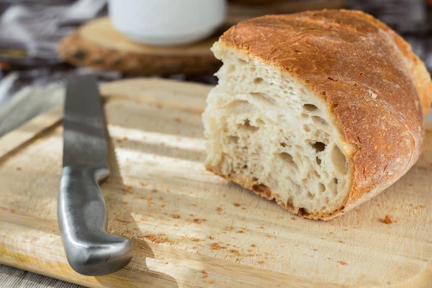 Foto de uma tábua de madeira, com uma faca de cortar pão e um pedaço de pão em cima.