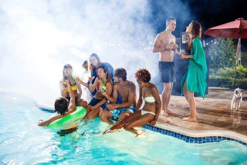 Pessoas bebendo em festa na piscina à noite.