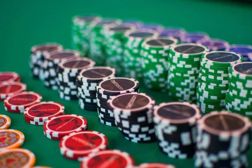 Imagem mostra fichas de diversas cores dispostas sobre um pano verde.
