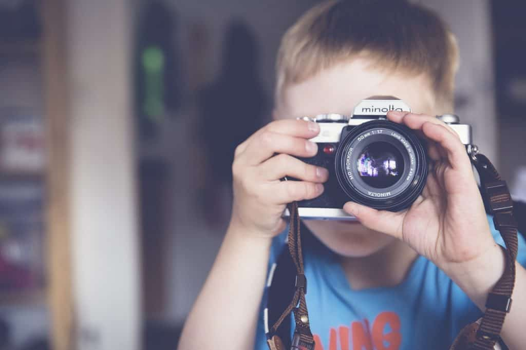 menino tirando foto com a mão na lente