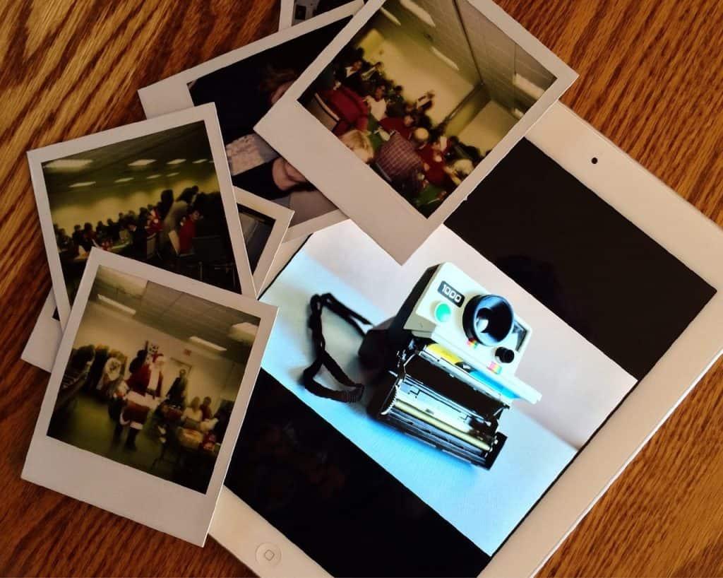 Tablet exibindo a imagem de uma câmera instantânea e fotos impressas ao lado