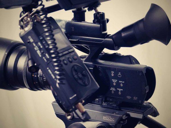 A imagem mostra um gravador de voz junto a uma câmera de vídeo.