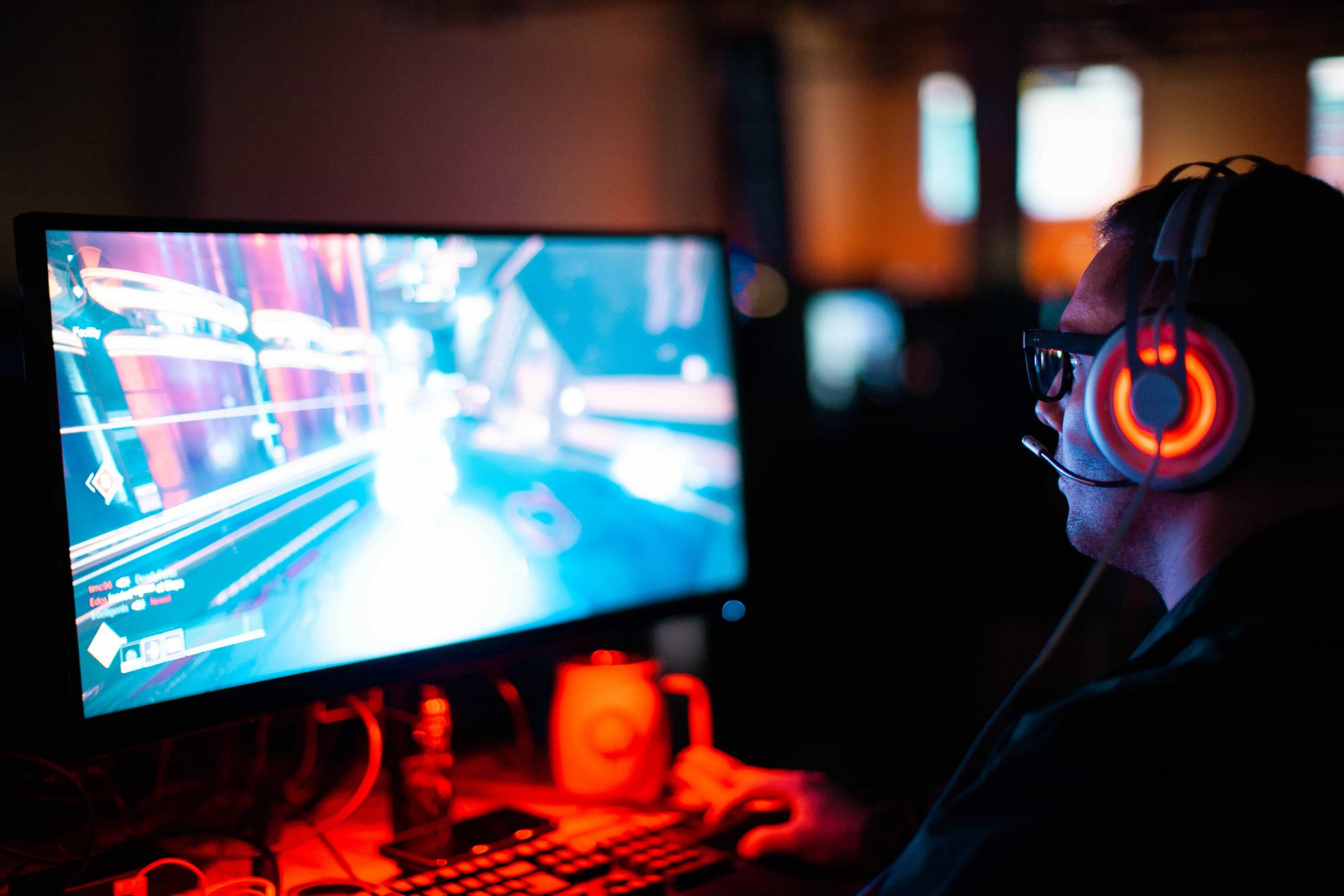 Image shows a player in front of a PC monitor using a white gamer headset with orange lighting.