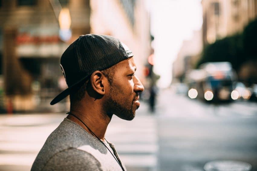 Imagem mostra um homem usando um Trucker preto com fechamento em Snapback. Ao fundo, o movimento de um cenário urbano, desfocado.