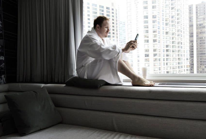 Homem vestindo roupão branco sentado na beira de uma janela mexendo no celular.