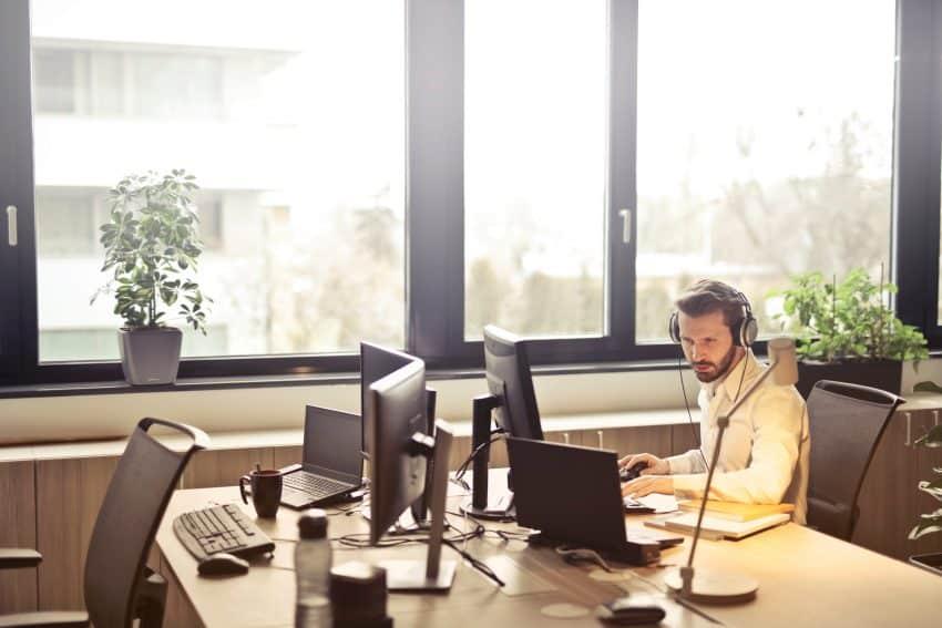 Homem sentado em escritório, ao computador, utilizando o fone de ouvido com microfone.