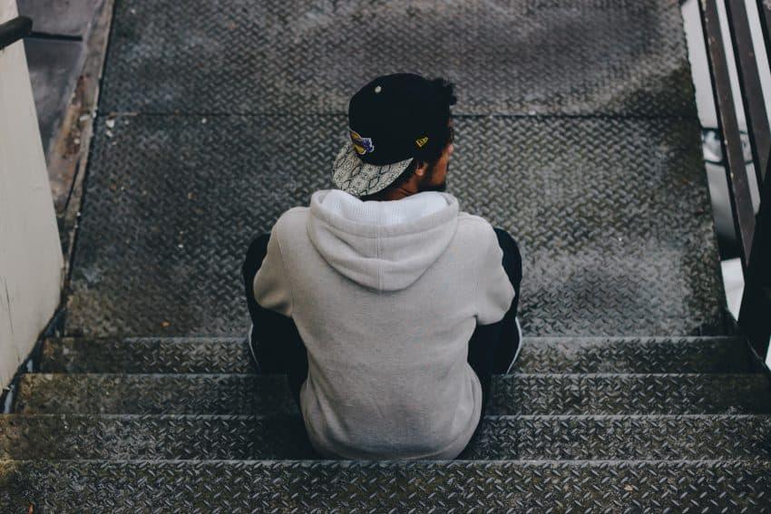 Imagem mostra um homem sentado, centralizado em meio à uma escada com degraus de metal. De costas, ele usa um aba reta preto virado para trás, com a aba colorida e estampada.