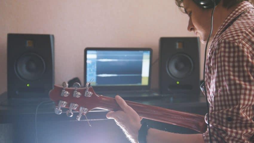 Homem tocando violão em frente ao computador com caixa de som.